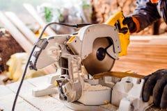 Carpenter working. Man cutting plank by circular saw. Stock Photos