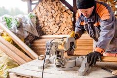 Carpenter working. Man cutting plank by circular saw. Royalty Free Stock Image