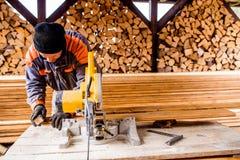 Carpenter working. Man cutting plank by circular saw. Royalty Free Stock Photos