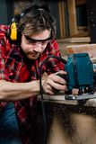 Carpenter working of manual hand milling machine in the carpentry workshop. joiner. stock images
