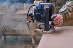 Carpenter working with manual hand milling machine in the workshop. Wooden furniture manufacturing process stock image