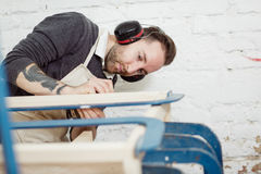 Carpenter is working on new wooden product. Royalty Free Stock Images