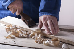 Carpenter working with plane on wooden background at Building Site. Joiner workplace Royalty Free Stock Image