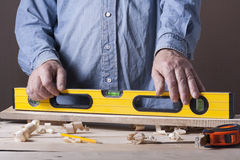 Carpenter working with plane on wooden background at Building Site. Joiner workplace Royalty Free Stock Images
