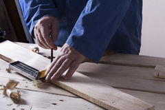 Carpenter working with plane on wooden background at Building Site. Joiner workplace Stock Photos