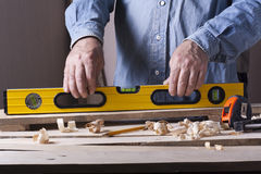 Carpenter working with plane on wooden background at Building Site. Joiner workplace Royalty Free Stock Photo