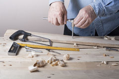 Carpenter working with plane on wooden background at Building Site. Joiner workplace Stock Photography