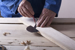 Carpenter working with plane on wooden background at Building Site. Joiner workplace Stock Image