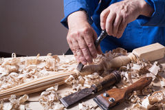 Carpenter working with plane on wooden background at Building Site. Joiner workplace. Royalty Free Stock Images