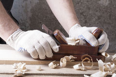 Carpenter working with plane on wooden background at Building Site. workplace Royalty Free Stock Photography