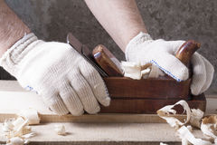 Carpenter working with plane on wooden background at Building Site.  workplace Stock Photography