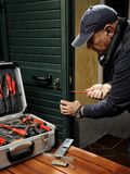 Carpenter working the replacement of the lock of a door. Stock Photos