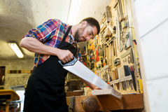 Carpenter working with saw and wood at workshop Stock Photo