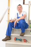Carpenter. Working with screwdriver and other tools on stairs Stock Photo