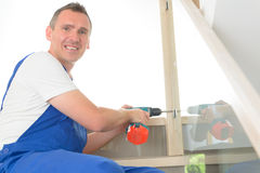 Carpenter. Working with screwdriver on stairs Royalty Free Stock Images