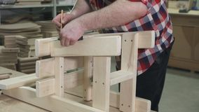 Carpenter working in a shirt with a beard in the workshop makes a wooden chair stock footage