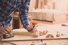 Free Carpenter Working With Meter Or Rule Taking Measures On Wood Using Pencil. Workshop Background Stock Image - 140979091