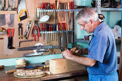 Carpenter working with wood. Cabinetmaker sanding a piece of wood in his workshop with tools on the background. carpenter working with wood Royalty Free Stock Photography
