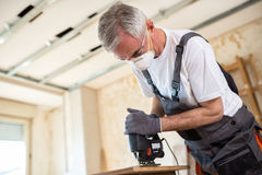 Carpenter working with wood plank at workshop royalty free stock photos