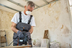 Carpenter working with wood plank at workshop stock photo