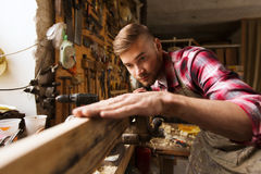Carpenter working with wood plank at workshop. Profession, carpentry, woodwork and people concept - carpenter testing wood plank evenness at workshop Royalty Free Stock Photography