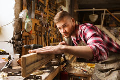 Carpenter working with wood plank at workshop. Profession, carpentry, woodwork and people concept - carpenter testing wood plank evenness at workshop Royalty Free Stock Photos