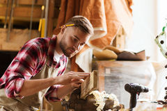 Carpenter working with wood plank at workshop. Profession, carpentry, woodwork and people concept - carpenter testing wood plank evenness at workshop Stock Photo