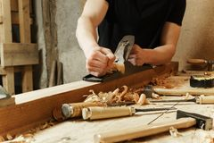 Carpenter working a wooden board with a plane royalty free stock photo