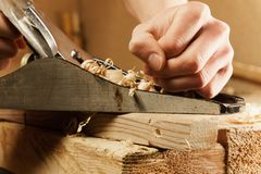 Carpenter working a wooden board with a plane stock image