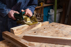 Carpenter Working on a Wooden Boards in his Workshop Royalty Free Stock Photography