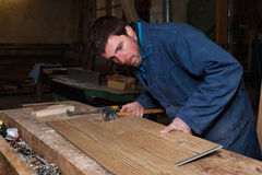 Carpenter working on a Wooden Boards in his Workshop Stock Photo