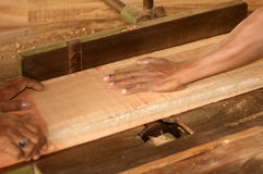 Carpenter working on a wooden plank Stock Image
