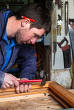 Carpenter working on a Wooden Window Frame in his Workshop. Portrait of a Carpenter wearing Blue Overalls working on a Wooden Window Frame with a Hammer in his Royalty Free Stock Photography