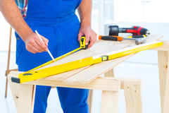 Carpenter working at workbench in office. Midsection of carpenter working at workbench in bright office Stock Photo