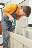 Carpenter works with drill Stock Image