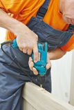 Carpenter works with drill Royalty Free Stock Image