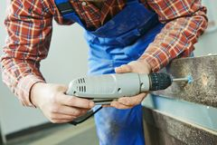 Carpenter works with drill Stock Photography