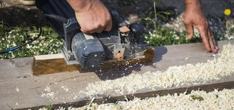 Carpenter works with an electric tool royalty free stock images