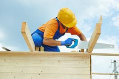 Carpenter works with hand saw. Construction roofer carpenter worker sawing wood board with hand saw on roof installation work Stock Photography