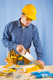 Carpenter works with handsaw Stock Photos