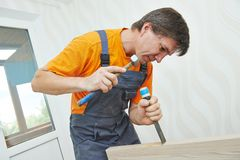 Carpenter works with hummer and chisel Stock Image