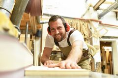 Free Carpenter Works In A Joinery - Workshop For Woodworking And Sawing Royalty Free Stock Image - 125321536