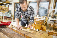 Carpenter works with musical instruments in workshop Royalty Free Stock Image