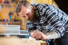 Carpenter works with plane on wood plank in workshop Stock Photos
