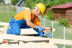 Carpenter works on roof. Construction carpenter worker nailing wood board with hammer on roof installation work Stock Photo