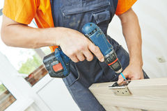 Carpenter works with scredriver Royalty Free Stock Photos