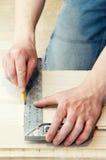 Carpenter works using metal angle Royalty Free Stock Image