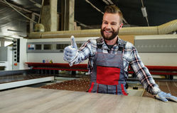 Carpenter works on wood plank in carpentry workshop Stock Photos