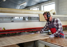 Carpenter works on wood plank in carpentry workshop Royalty Free Stock Image