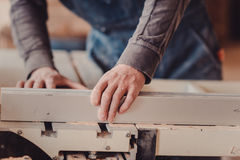 A carpenter works on woodworking the machine tool. Carpenter working on woodworking machines in carpentry shop. Royalty Free Stock Image